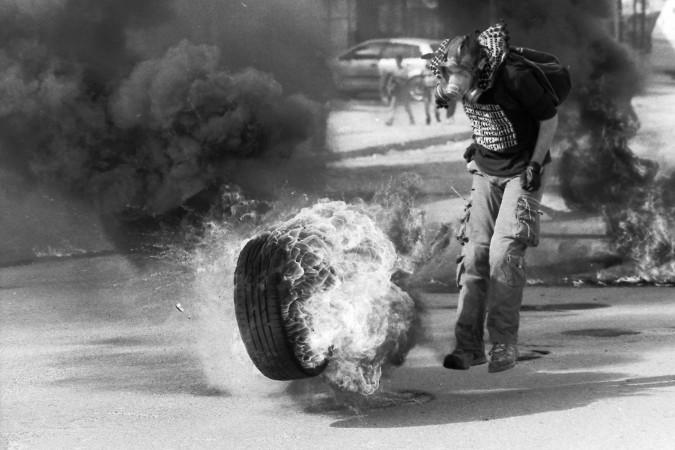 ISRAEL, 14. Dezember 2014 - Checkpoint von Qalandiya. Junge versucht einen brennenden Reifen in Richtung Checkpoint/Soldaten rollen zu lassen. (Bild: Emmanuele Contini)